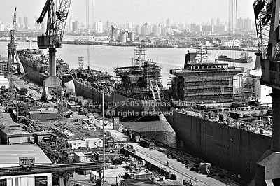 The old shipyards along the Huangpu river are being dismantled, giving way to the Expo 2010. Most shipyards have been moved to the Yellow River, where land is cheaper and in ample supply. In this image, a massive tanker is floating next to smaller vessels in the docks, while material is piled high on shore.