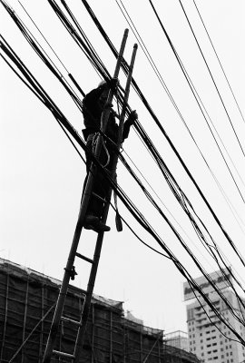 Repairs to the electrical wiring are often made with rather little precautions. A wooden ladder leaning against the wires, a hemp rope and the work can begin. 