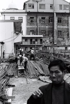 A construction site in downtown Shanghai. While workers in the background clamber over mountains of steel, the guard has a bad day.