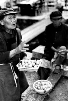 An old woman on the market haggles over her eggs. The markets are full of small stalls, with colorful produce and people bringing it in on tricycles and scooters.