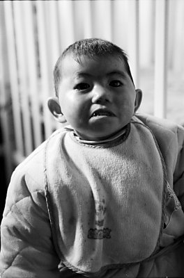 A child in an orphanage in Shanghai is looking straight at the viewer. With little hope of adoption these children have little to look forward to and their nurses are constantly looking for better food, diapers and more to help them survive another few months.