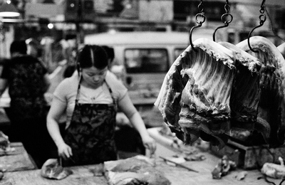 Three sides of meat are hanging from old, hand smithed hooks in a wet market in Shanghai. In the background, a woman is looking at a hunk of meat to figure out how to cut it up.