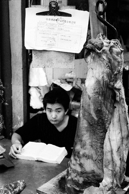 Deep in thought, a young man is studying his books at the market, while he is waiting for customers to buy  meat. A large, official notice is posted prominently to show that he is legit and his wares are fresh.