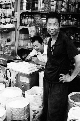 Standing amidst his goods, a trader in rice, beans, oil and other canned goods smiles at the camera. Their stall was stuffed to the rafters with bottles and cans, sacks of rice and drums full of oil. The small counter features a poster with a modern, beautiful woman, electronic scales and a small assortment of noodles.