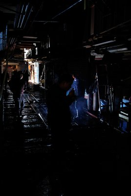 The fish market in Shanghai is full of gritty images, smiling people and fish. Busy in the early morning, it all quiets down around 7am. Then the corrugated steel plates come up and get washed and the repairs get done. In this image, a welder fixes the rails under the steel plates and basks everything in the light from his torch.