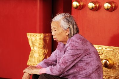 An old lady rest in front of the great doors of the big building at the entrance. The red and gold color theme of the doors balances with her gray-white hair. Many old people come to the forbidden city every day, some from far away to see it for the first time, others from Beijing te relish its past.
