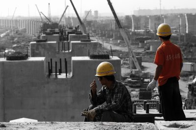 From atop an almost finished pillar, two workers gaze out as the construction site stretches out into the distance of Shanghai. On the left, the big new station will arise. Meanwhile, the workers still have a long way to go to connect Shanghai and Beijing.