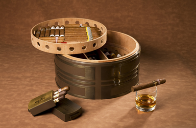 The Double Happiness, with detached case for three cigars, has the build of a tank and the lightness of Okoume wood. The outside is a formidable round shape, the light wraps around it and plays on its features.