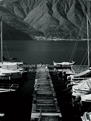 The old wood on the boat landing on the Lago di Como shines in the sunshine, while the lake lies black, awaiting a summer.